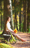 Girl on Bench. Beautiful girl with leaves sitting on bench in autumn park Stock Photography