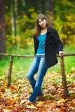Girl on Bench. Beautiful girl sitting on fence in autumn park Stock Photo