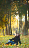 Girl on Bench. Beautiful girl sitting on grass in autumn park Royalty Free Stock Photos