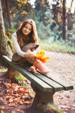 Girl on Bench. Beautiful girl with leaves sitting on bench in autumn park Stock Photo