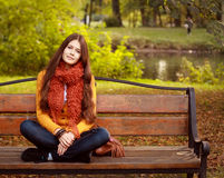 Girl on bench in autumn park Stock Photography