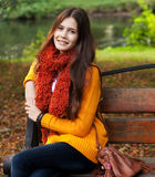 Girl on bench in autumn park Stock Photo