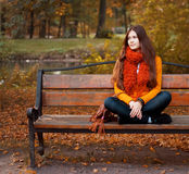Girl on bench in autumn park Royalty Free Stock Images