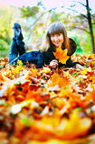 Girl on a Bench. Beautiful girl lying on a glade in autumn forest Stock Photo