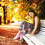 Girl on a Bench. Beautiful girl sitting on a bench in autumn park Stock Photography