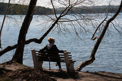 Girl on a bench by the lake Stock Photos