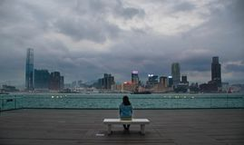 A girl on a bench looking at the Hong Kong skyline. A lone girl looking at the Hong Kong skyline Royalty Free Stock Photography