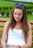 Girl on the bench with mobile phone. Royalty Free Stock Image