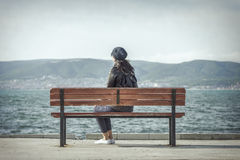 Girl on the bench near the sea. Royalty Free Stock Photos
