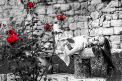 Girl on the bench near the wall. Girl on the bench near wall, black and white shot with red flowers Royalty Free Stock Photo