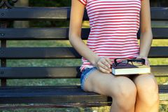 The girl on a bench in the park with a book and black glasses in her lap. A student in the park reading a book.  Stock Photography