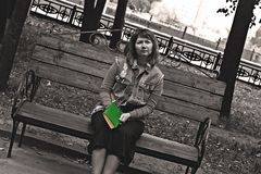 Girl on a bench in the Park with a book in her hands, black and white photo royalty free stock image