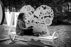 Girl on a bench in the Park with a book in her hands, black and white photo royalty free stock photo