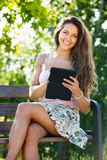 Girl on bench in park with ereader Stock Images