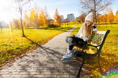 Girl on the bench with roller blades Royalty Free Stock Image