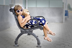 Girl on the bench. Girl sitting on a bench in the park summer day Royalty Free Stock Photos