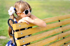 Girl on the bench. Girl sitting on a bench in the park summer day Royalty Free Stock Photography