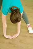 The girl bended down doing the exercise. In the sports club indoors royalty free stock image