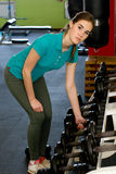 The girl in bended position trying to pick up the dumbbells Royalty Free Stock Images