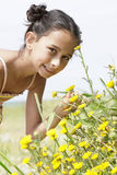 Girl Bending Down To Smell Flower In Field Stock Images
