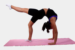 Girl bending over backwards. Young flexible woman wearing workout attire bending backwards while pointing foot standing on pink yoga mat stock photo