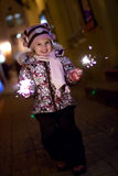 Girl with Bengal light. Beautiful little girl with two Bengal lights in her hands at New Year royalty free stock image