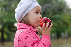 Girl in beret with apple Stock Images