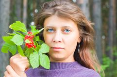 The girl with berries. Against wood royalty free stock image