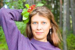 The girl with berries. Against wood, Smiles royalty free stock image