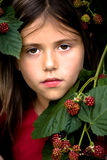 Girl betwin blackberries Stock Photography