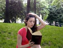 Girl with Bible. In park.  Photographed in Central Park,  New York, USA.  She was in her twenties at the time of shoot.  Taken June, 2007 Stock Photo