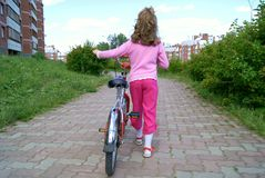 The girl with a bicycle. The child goes on sidewalk with a bicycle having turned a back Stock Photos