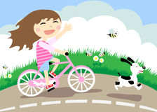 Girl on a bicycle. The girl goes on bicycle on road, running dog Stock Photos