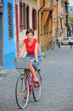 Girl with bicycle. Retro girl with bicycle in old town scenery Royalty Free Stock Photos