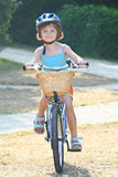 Girl bicycle 3. A young girl with a blue helmet approaches on her bicycle with a wicker basket in front stock photo