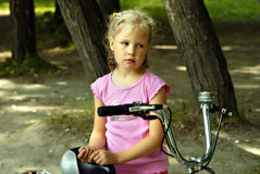 Girl with bicycle. Sad girl with bicycle in park Royalty Free Stock Image