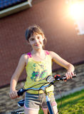 Girl on a bicycle against the brick wall at house Stock Image