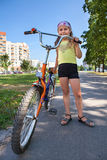 Girl with a bicycle on an asphalt track in park Stock Photo