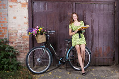 Girl with a bicycle and a basket of flowers reading the book on Royalty Free Stock Image