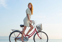 Girl and bicycle. Beautiful red-haired girl in the authentic bike on the beach stock image