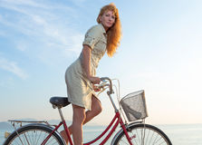 Girl and bicycle. Beautiful red-haired girl in the authentic bike on the beach royalty free stock image