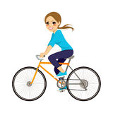 Girl On Bicycle. Beautiful young girl riding bicycle happy side profile view Stock Photo