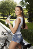 Girl with bicycle and bottle of water Royalty Free Stock Photos