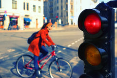 The girl on a bicycle on a city street at a red traffic light Royalty Free Stock Photos