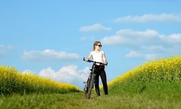 Girl with bicycle on a dirt road in rapeseed field. Stock Photo