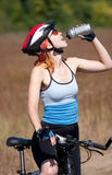 The girl by bicycle. Drinks water Royalty Free Stock Photography