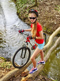 Girl on bicycle fording throught water on log . Royalty Free Stock Image