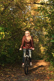 Girl on bicycle in forest Stock Photography