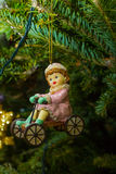 Girl on a bicycle - fur-tree toy on the branches of a live Christmas tree Royalty Free Stock Images