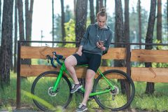 Girl on a bicycle in a grey hoodie in the park. Races on a bicycle. Active way of life and playing sports. Summertime Royalty Free Stock Image